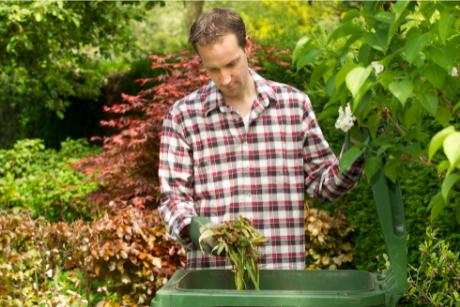man in garden putting weeds into green bin